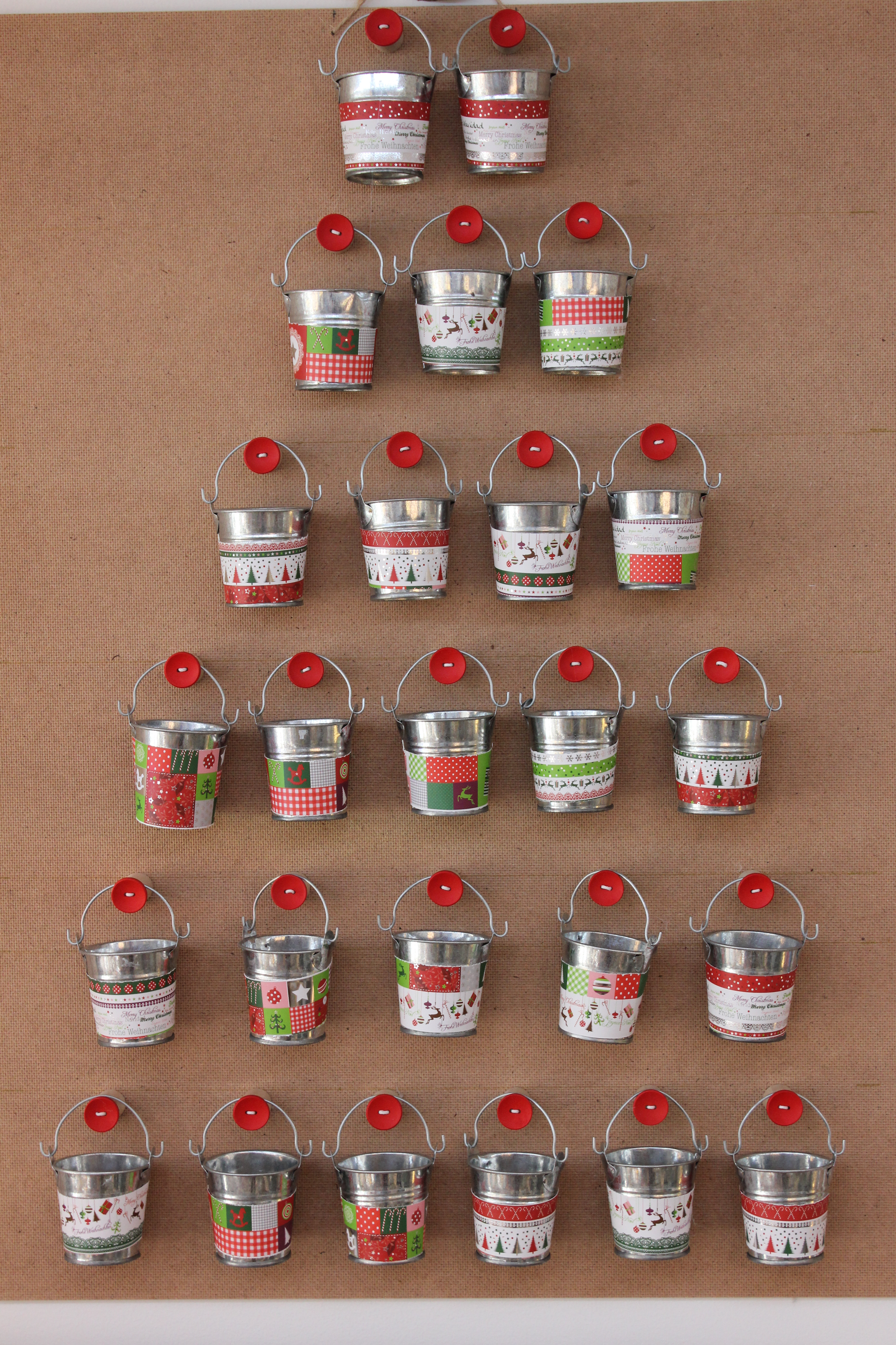25 small zinc buckets, decorated with coloured paper, hung on large ...